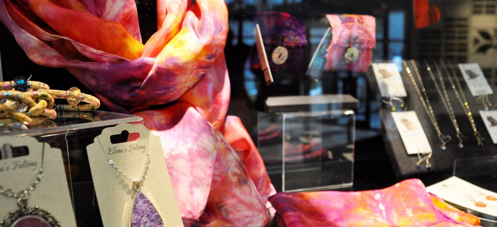 Scarfs and jewellery in gift shop display.